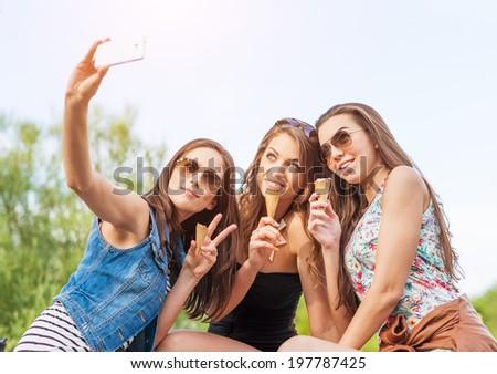 Three beautiful woman eating ice cream during selfie doing photo  - stock photo