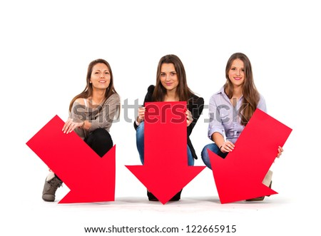 Three beautiful women holding arrows pointing down - stock photo