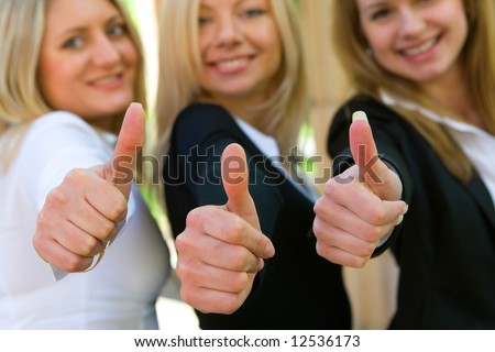 Three beautiful women holding thumbs up - stock photo