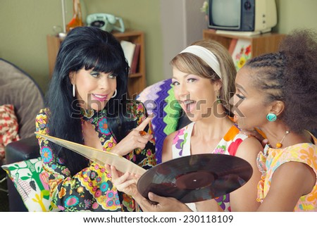 Three beautiful women in 1960s style talking about record - stock photo