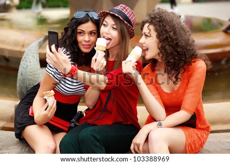 three beautiful women photographing themselves eating icecream