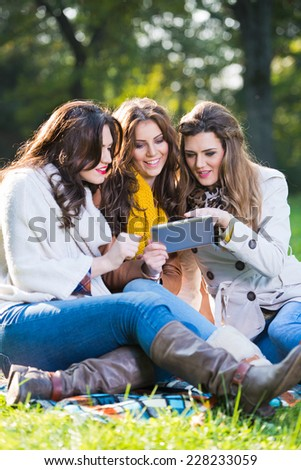 Three beautiful women using a tablet in the park