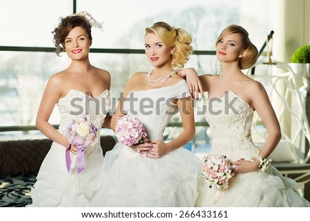 Three beautiful women wearing bridal gowns and holding wedding bouquets in interior - stock photo