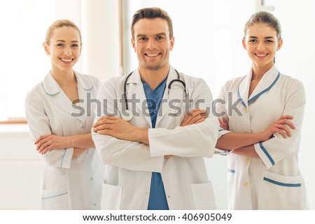 Three beautiful young doctors are looking at camera and smiling, standing with crossed arms in hall of the hospital - stock photo