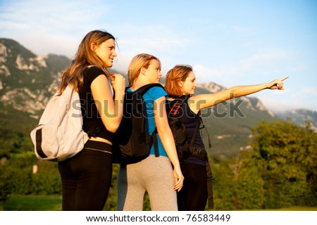 Three beautiful young girls on a trip in nature - stock photo