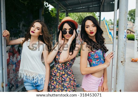 Three beautiful young girls posing at the bus stop - stock photo