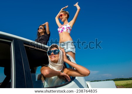 Three beautiful young model girls having fun traveling on a white car. They go against the background of fields with yellow flowers - stock photo