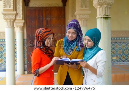 Three beautiful young muslim businesswoman sharing info - stock photo