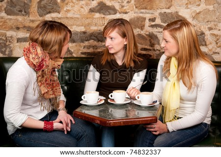 Three beautiful young students drinking  cappuccino and having a debate in coffee shop