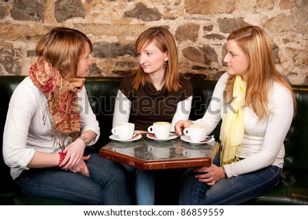 Three beautiful young students waiting drinking  cappuccino and having a debate in coffee shop