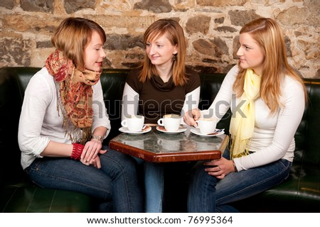 Three beautiful young students waiting drinking  coffee and having a debate in coffee shop