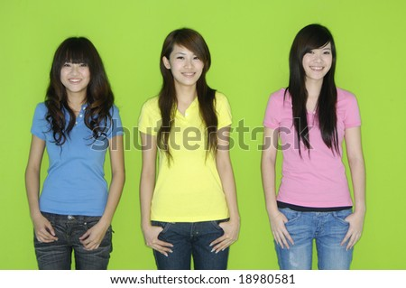 Three beautiful young women in studio over green background - stock photo