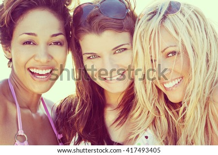 Three beautiful young women in their twenties laughing and having fun at a beach, shot in golden evening sunshine.