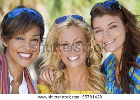 Three beautiful young women in their twenties laughing and having fun on vacation, shot in golden sunshine in a tropical resort location. - stock photo