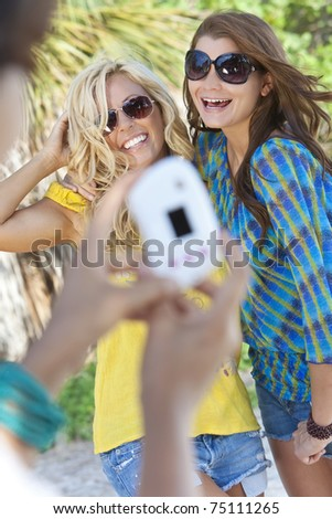 Three beautiful young women in their twenties laughing and having fun taking digital photographs on vacation, shot in golden sunshine in a tropical resort location. - stock photo