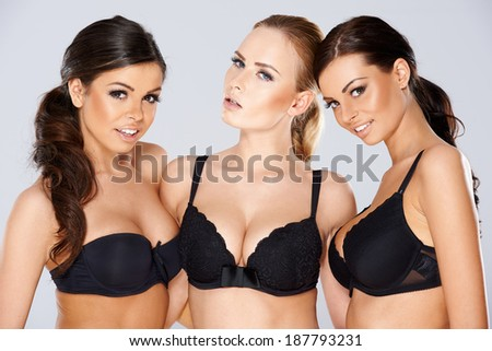 Three beautiful young women modeling black lingerie wearing black lacy bras looking off to the side of the frame with charming smiles - stock photo