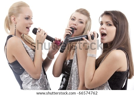 Three beautiful young women singing in microphones - stock photo