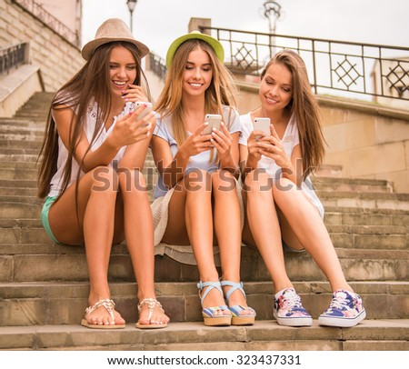 Three beautiful young women walk in the city, using phone outdoors