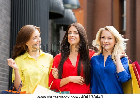 Three beautiful young women walking in the city center with shopping bags.