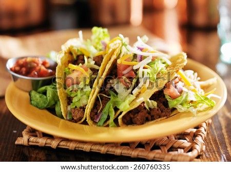 three beef mexican tacos with cheese and lettuce - stock photo
