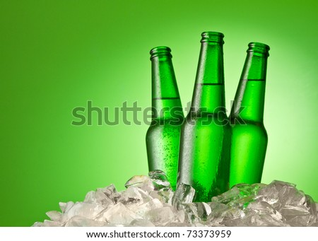 Three beer bottles getting cool in ice cubes. Isolated on a green. - stock photo