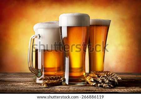 Three beers and wheat on a yellow background - stock photo