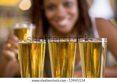 Three beers in a row, with young woman in background - stock photo