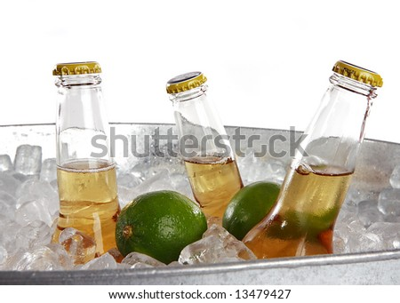 Three beers on ice with two limes - stock photo
