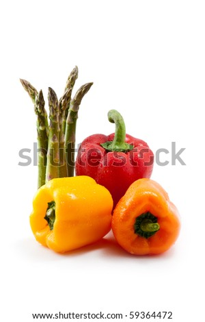 three bell peppers with asparagus on white with droplets of water - stock photo