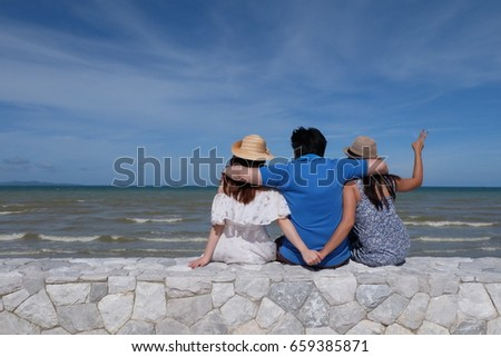 Three best friends breath fresh air, feel relax and think about the future with blue sky and great ocean sea in front