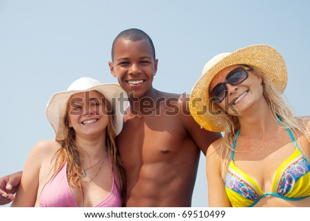 Three best friends having a laugh on the beach - stock photo