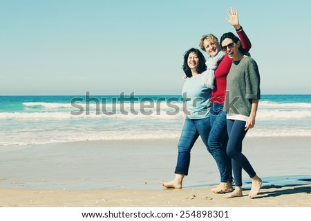 Three best friends walking at seaside - stock photo