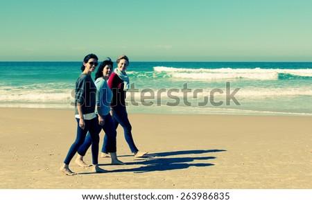 Three best friends walking at seaside - stock photo