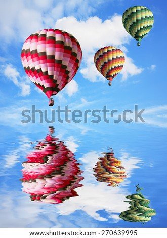 Three big balloons in the blue sky are reflected in water - stock photo