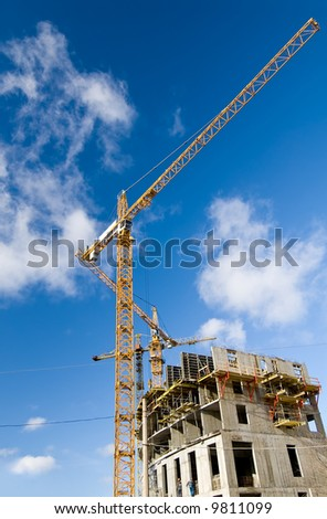 three big crossed yellow cranes at the construction place - stock photo