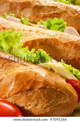 Three big sandwiches with chicken and with cheese and tomatoes - stock photo