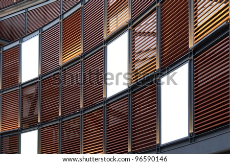 Three big vertical / portrait orientation blank billboard on modern brown wall - stock photo
