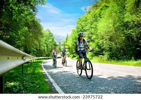 three bikers on forest road - stock photo