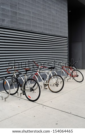Three bikes are locked to a modern looking sidewalk rack in Toronto - stock photo