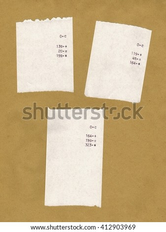 Three bills or receipts isolated over light brown background - stock photo