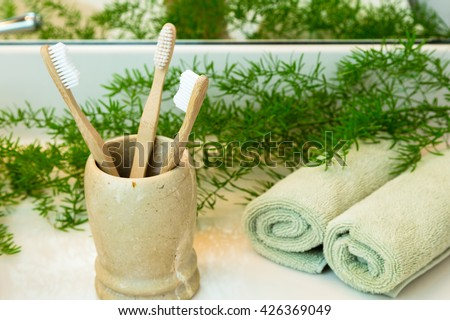 Three bio-degradable, compostable bamboo toothbrushes in marble cup. Rolled green towels in a spa setting. Green plant decor in background. Bathroom white countertop.