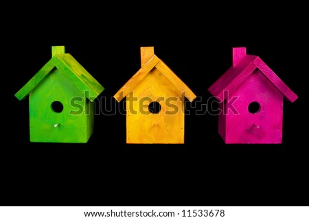 Three birdhouses on black background - stock photo