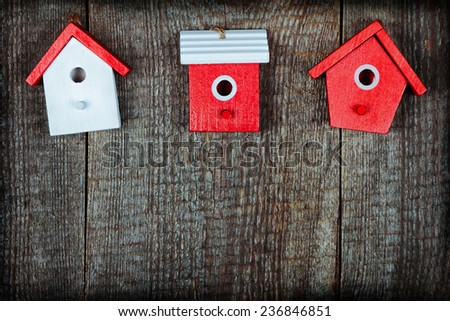 Three birdhouses painted with red and white colors on old wooden background - stock photo