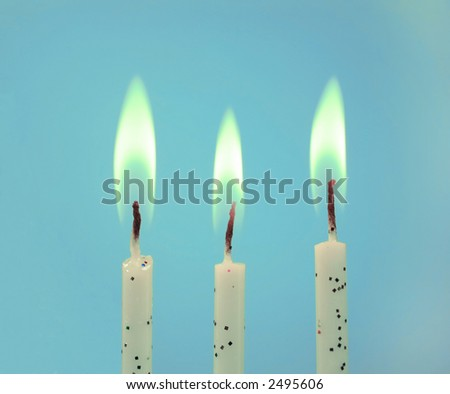 Three birthday candles on a blue background. - stock photo