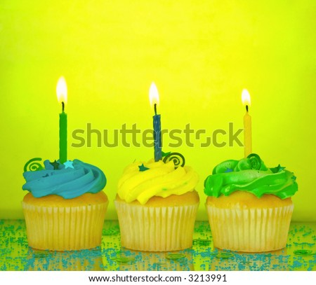 Three birthday cupcakes in blue, green, and yellow with lit candles, confetti, and sprinkles on a mirrored background