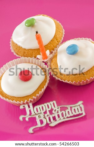 Three birthday iced buns with a candle - stock photo