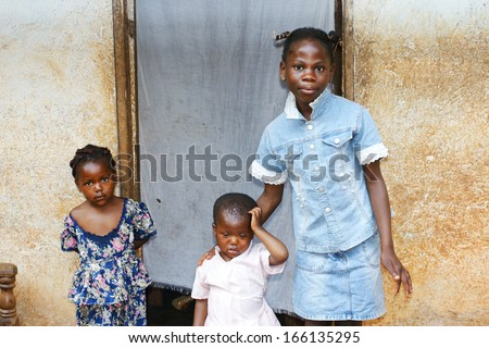 Three black African girls, sisters from a larger family, by their house's doorway