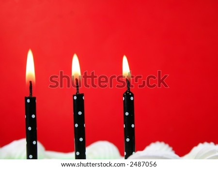 Three black and white candles on a birthday cake. - stock photo