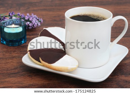 Three black and white cookies with a cup of coffee. - stock photo