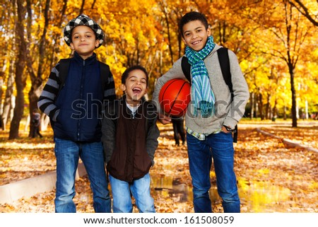 Three black boys, brother 5 8 10 years old standing with basketball ball in autumn park with orange maple trees smiling and laughing - stock photo